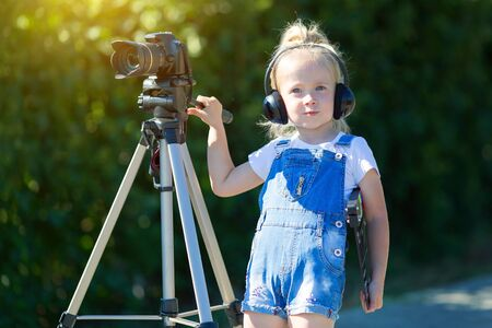 Child novice video blogger with a camera and a tripod. Little girl in headphones with camera