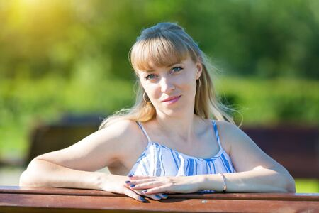 Portrait of a woman of Caucasian nationality on a summer sunny day in the park against the backdrop of greenery.
