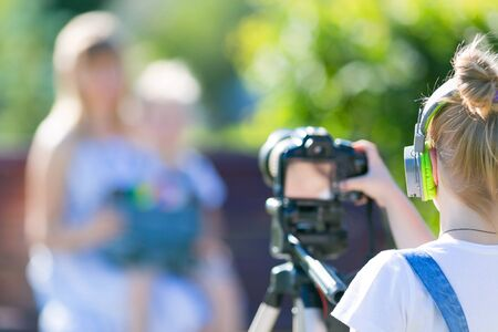 Girl novice videoblogger shoots at the camera, defocus. The child in the city park.