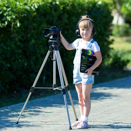 Child novice video blogger with a camera and a tripod. A little girl in headphones with a camera. Stock Photo