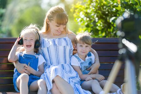 Happy young mother with children in front of a video camera. A beautiful woman with two daughters is shot in a TV program, sits in front of a photo camera on park bench.