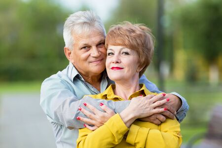 Family life of people of retirement age. An elderly man hugs his wife from behind tightly.