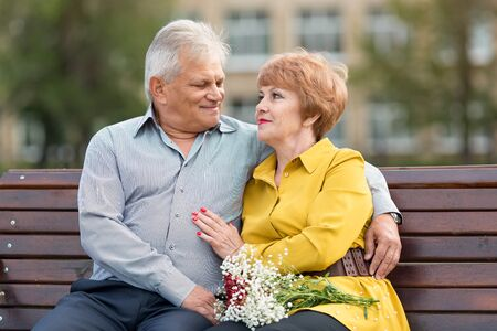 Family of senior citizens cuddling on bench in a city park Elderly people are hugging each other.