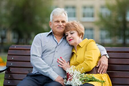 Elderly people are hugging each other. Family of senior citizens cuddling on a bench in city park. Фото со стока