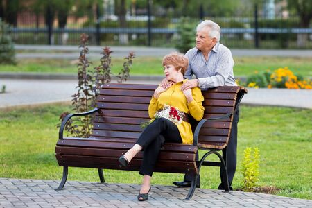 An old woman sits on bench and her husband stands next to her and hugs his shoulders An elderly man gently hugs his wife over his shoulders. Imagens