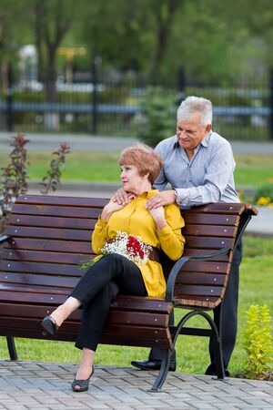An elderly man gently hugs his wife over his shoulders. An old woman sits on a bench and her husband stands next to her hugs his shoulders.