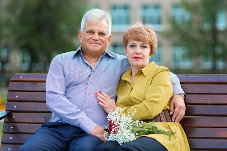 Elderly people are hugging each other. Family of senior citizens cuddling on a bench in a city park.