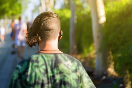 View from a pin on a man with a short haircut on his head as he walks along the street. Back view of a young man with creative haircut. Reklamní fotografie