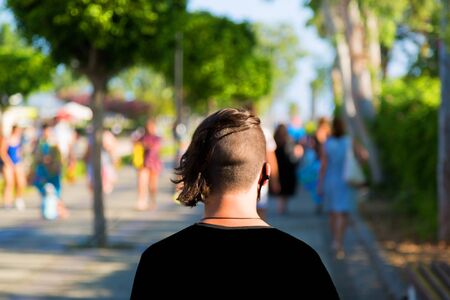 Back view of a young man with creative haircut. View from pin on a man with a short haircut on his head as he walks along the street