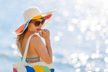 Sexy woman shy and modest with glasses wearing a hat and bag The girl in the hat and beach bag smiles cute. 版權商用圖片