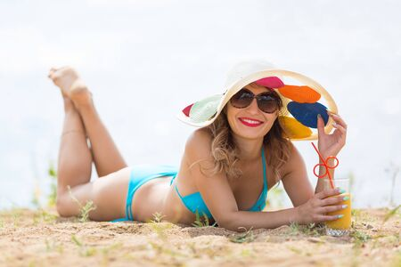 Girl with a glass of juice on the beach. A woman in a hat lies on the beach drinks pineapple juice Imagens
