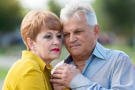 Beautiful married couple of seniors. Senior citizen in blue shirt and an elderly wife in a yellow dress outdoors