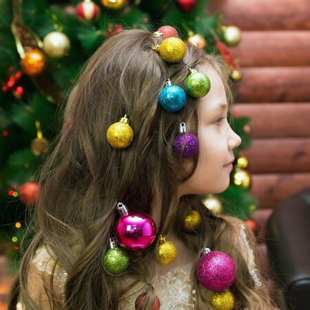 Girl with Christmas decorations her head Little girl with garlands and holiday balls into her hair with Christmas decorations