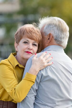 An elderly wife hugs her husband with a gray head. A gray-haired man with his wife on the street.