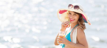 Sexy brunette with juice on the beach. A girl of European appearance in a bright beautiful hat drinks apricot juice through a straw on beach