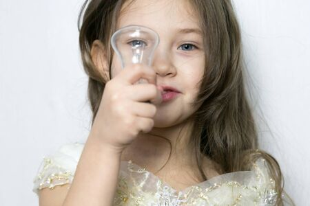 A little girl holds an incandescent lamp her hand and looks through it around Girl with a light bulb in her hands.