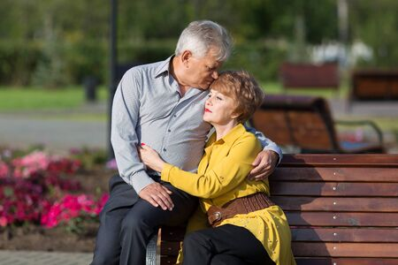 A married couple of pensioners on a bench. Mature lovers hug tightly on a bench in a city park. Stock Photo
