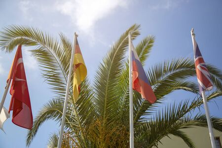 Four flags of Turkey, Russia, UK, Germany against the background of palm trees and sunny sky.