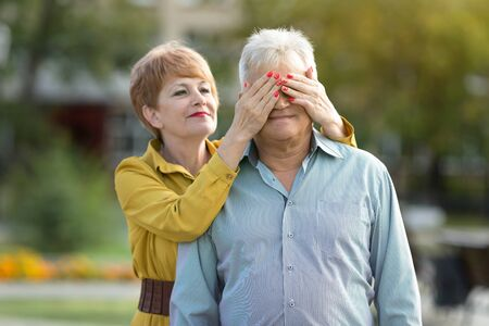 Elderly married couple outdoors. A woman of age gently covers her retirees eyes with her husband. Zdjęcie Seryjne