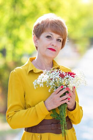 Portrait of an old woman with a bouquet. Beautiful woman aged 55-65 years holds bouquet of flowers in her hands