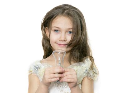 Girl with an electric lamp in her hands. Caucasian girl 5-7 years old in a beautiful white dress plays with an incandescent lamp. Imagens