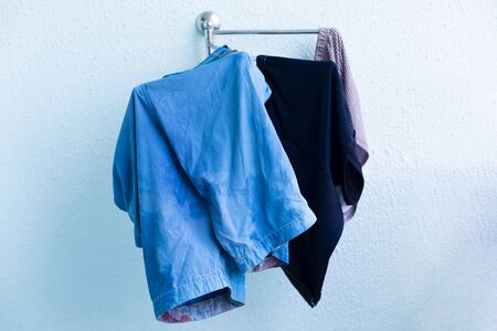 Wet clothes are hanging on the dryer. Mens swimming trunks and shorts are dried on the balcony of the hotel. Zdjęcie Seryjne