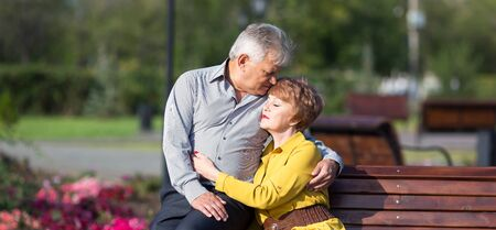 Adult lovers met in the park, Man and woman aged on a first date, Reklamní fotografie - 133282188