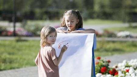 A girl poses as a model to her friend he paints her portrait, Little boy draws his sister as a model