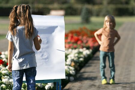 The boy poses as a model for his girlfriend, she paints his portrait, A little girl draws her brother as a model