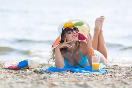 The girl lies on the beach with a glass of juice. Pretty woman 30 years, old blue bikini sunbathes on the beach holds juice in her hand Zdjęcie Seryjne