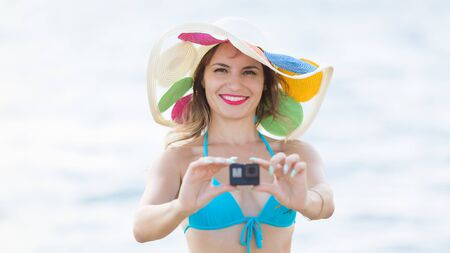 Girl with a mini video camera on the beach, A woman in a hat and bikin filming a vacation video, Zdjęcie Seryjne