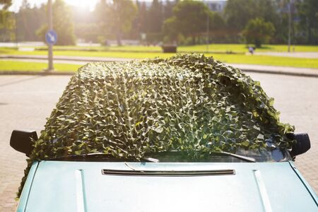 Car under camouflage net on the street. The car is covered with a protective camouflage net to protect from sunlight and high temperature.