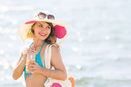 Sexy brunette with juice on the beach A girl of European appearance in a bright beautiful hat drinks apricot juice through a straw on beach,