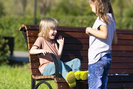 Children laugh outdoors in the park. Boy and girl are friends, play, laugh in the summer on the street.