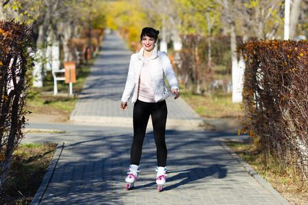 Girl learns to skate, sunny day A young woman in white jacket trousers skates for the first time. Zdjęcie Seryjne