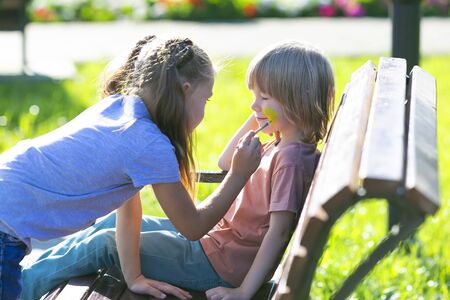 A little girl is applying aqua makeup to face of a 5 year old boy who is sitting on a bench in park.
