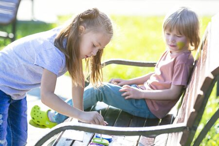 A little girl is applying aqua makeup to the face of a 5 year old boy who is sitting a bench in a park. Sister paints on brothers face. Zdjęcie Seryjne