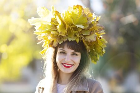 Girl with a wreath of leaves on her head. The woman made a hat from autumn fallen leaves for head