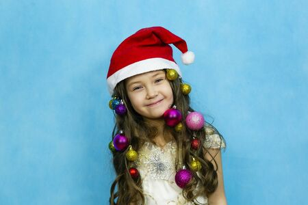 A girl with Christmas toys braided in hair is laughing on a blue background. Girl in santa claus hat on a blue background.
