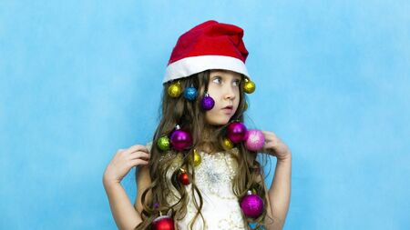 girl with Christmas toys braided in hair is laughing on a blue background Zdjęcie Seryjne