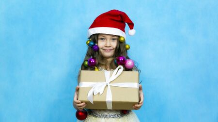A child in a red hat with a New Years gift in his hands. Girl in a Christmas hat with toys in her hair holds a gift in paper packaging on a blue background