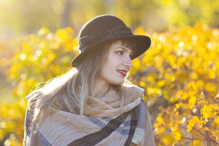Autumn portrait of a dreaming woman. A girl of 30-35 years old looks thoughtfully at the autumn yellow leaves. Zdjęcie Seryjne