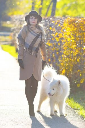 A girl in a coat and hat with a white dog on a leash breathes fresh cool air in the park. Woman walk with a dog in the autumn city.
