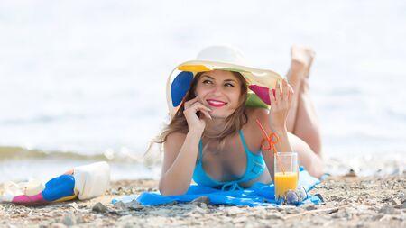 Pretty woman bikini sunbathes on the beach holds juice in her hand Zdjęcie Seryjne
