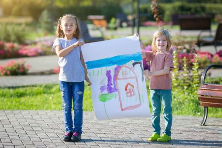 Preschool children have drawn a drawing and hold it in their hands while standing on the street. Children show a picture drawn by them in paints. Zdjęcie Seryjne