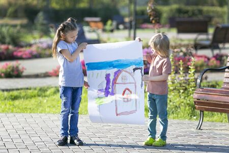 Children show a picture drawn by them in paints. Preschool children have drawn a drawing and hold it their hands while standing on the street