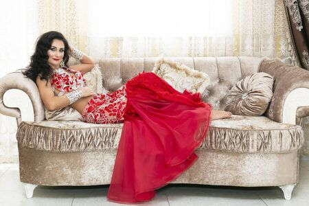 A brunette girl in a suit of oriental beauty lay on a beautiful rich sofa against the background of window with curtains Beautiful woman is lying on a luxurious sofa.