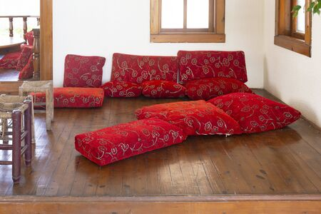 Red pillows on the floor and a low table are traditional attributes for relaxing in Muslim countries. A place for relaxing on the floor is an oriental tradition.