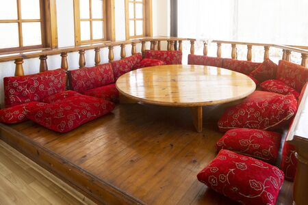 A place for relaxing on the floor is an oriental tradition. Red pillows on the floor and low table are traditional attributes for relaxing in Muslim countries