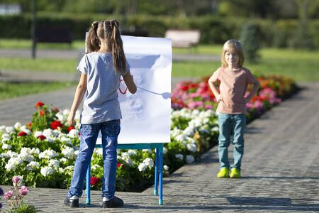 Children paint portraits of each other on the street. Brother and sister paint funny portraits people with paints on paper.